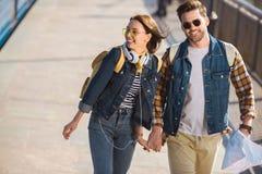 пары стильных туристов в солнечных очках с наушниками и картой рюкзаков на на открытом воздухе метро стоковое изображение