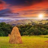 Пары стогов сена и дерева на горе на заходе солнца Стоковое Изображение RF