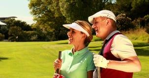 Пары стоя на поле для гольфа смотря вперед видеоматериал