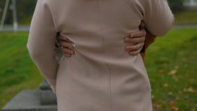 Пары стоя на улице и обнимать Укомплектуйте личным составом объятия взгляд женщины от задней части крупный план рук женщины обним Стоковые Изображения