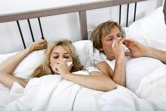 Пары страдая от холодный лежать на кровати стоковые изображения rf