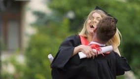 Пары студент-выпускников наслаждаясь жизнью, обнимая и поворачивая вокруг, истинное счастье акции видеоматериалы