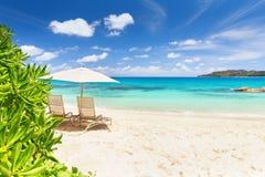 Пары стульев и зонтика на пляже острова Praslin, s Стоковое Изображение RF
