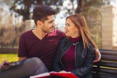 Пары студентов сидят на стенде в парке Стоковые Изображения RF