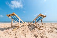 Пары стульев на песчаном пляже на солнечный день ища голубое Стоковые Изображения