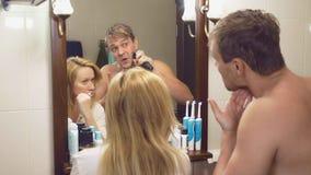 Пары, супруг и жена собирают в ванной комнате перед зеркалом стоковые изображения