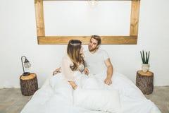 Пары счастливой девушки и парня усмехаясь в кровати дома стоковые изображения