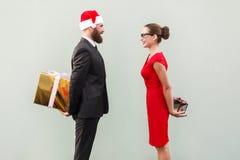 Пары счастья смотря один другого и держа подарочную коробку позади Стоковая Фотография RF