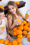 Пары с апельсиновым соком в кровати Стоковые Фото