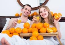 Пары с апельсиновым соком в кровати Стоковые Фотографии RF