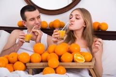 Пары с апельсиновым соком в кровати Стоковое Изображение