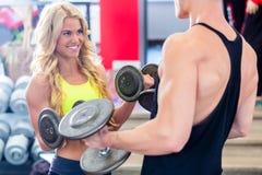 Пары с гантелями на спорте в спортзале фитнеса Стоковое фото RF