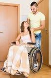 Пары с женщиной в кресло-коляске около двери Стоковые Изображения