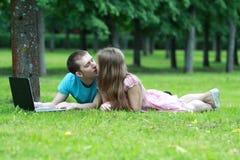 Пары с компьтер-книжкой в парке Стоковое Изображение