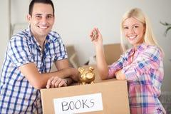 Пары с копилкой и ключи с moving коробками Стоковое фото RF
