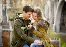 Пары с подняли в влюбленность целуя на переулке улицы празднуя день валентинок при страсть сидя на парке города Стоковые Фотографии RF