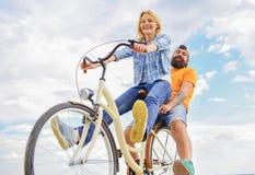 Пары с предпосылкой неба даты велосипеда романтичной Пары в задействовать даты влюбленности Исследуйте город Велосипед ренты чело стоковые фото