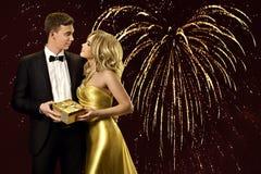 Пары с присутствующими подарочной коробкой, женщиной и человеком над светами сердца Стоковая Фотография