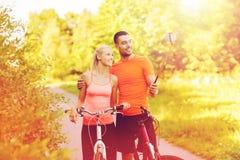 Пары с ручкой selfie велосипеда и smartphone Стоковая Фотография RF
