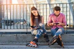 Пары с сидеть телефонов Стоковые Изображения