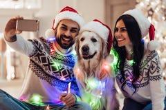 Пары с собакой на ` s Eve Нового Года Стоковые Изображения