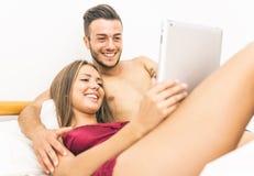 Пары с таблеткой в кровати Стоковое фото RF
