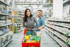 Пары с тележкой вполне товаров в супермаркете стоковые фотографии rf