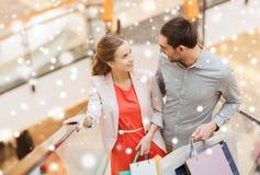 Пары с хозяйственными сумками на эскалаторе в моле Стоковая Фотография RF