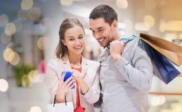 Пары с smartphone и хозяйственными сумками в моле Стоковое Изображение RF