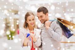 Пары с smartphone и хозяйственными сумками в моле Стоковая Фотография RF