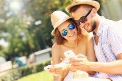 Пары с smartphones в парке Стоковое фото RF