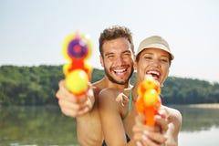 Пары с squirt оружи смеясь над счастливо Стоковая Фотография