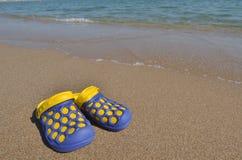 Пары тапочек пляжа приближают к морской воде Стоковые Фотографии RF