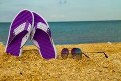 Пары темповых сальто сальто и солнечных очков на песочном море приставают к берегу Стоковое Фото