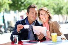 Пары туристов в кофе городка выпивая Стоковые Фото