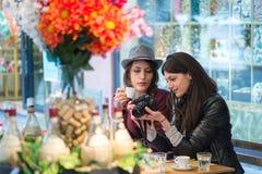 Пары туристов друзей сидя на баре ставят наблюдать на обсуждение изображения на мониторе SLR Стоковые Фотографии RF