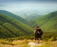 Пары туристов с рюкзаками na górze высокой горы стоковые фотографии rf