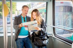 Пары туристов читая город составляют карту, едущ трамвай Стоковые Фотографии RF