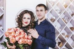 Пары укомплектовывают личным составом дают женщине букет роз цветков красивое стоковые изображения