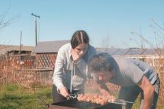 Пары укомплектовывают личным составом и мясо shashlik кашевара женщины na górze гриля угля на задворк Говорить и усмехаться совме стоковые фото