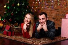 Пары укомплектовывают личным составом и ложь женщины около рождественской елки Стоковое Фото