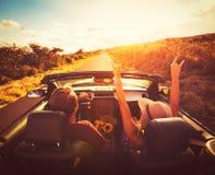 Пары управляя автомобилем с откидным верхом на заходе солнца Стоковое Изображение RF
