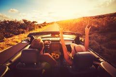 Пары управляя автомобилем с откидным верхом на заходе солнца Стоковая Фотография RF