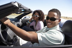 Пары управляя автомобилем с откидным верхом на дороге пустыни Стоковое фото RF