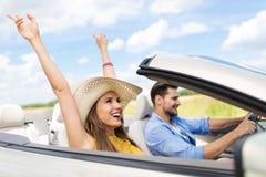 Пары управляя в автомобиле с откидным верхом стоковые фото