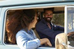 Пары управляя жилым фургоном усмехаясь на одине другого Стоковые Фото
