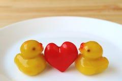Пары утки младенца с красным сердцем Marzipans, тайскими традиционными помадками Kanom-взгляда, который служат на белой плите Стоковые Изображения