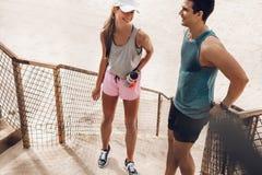Пары фитнеса отдыхая и говоря на пляже Стоковое фото RF