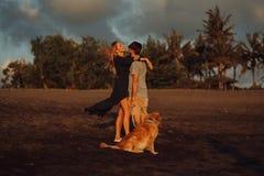 Пары хипстера красивого счастливого смеха молодые с золотым retriever на пляже океан песок Волны concepte свободы и стоковое фото rf