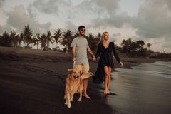 Пары хипстера красивого счастливого смеха молодые с золотым retriever на пляже океан песок Волны concepte свободы и стоковые фото